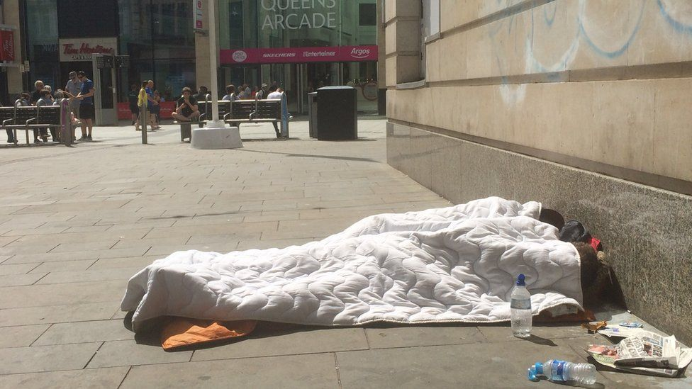 A homeless person trying to get shade in Cardiff