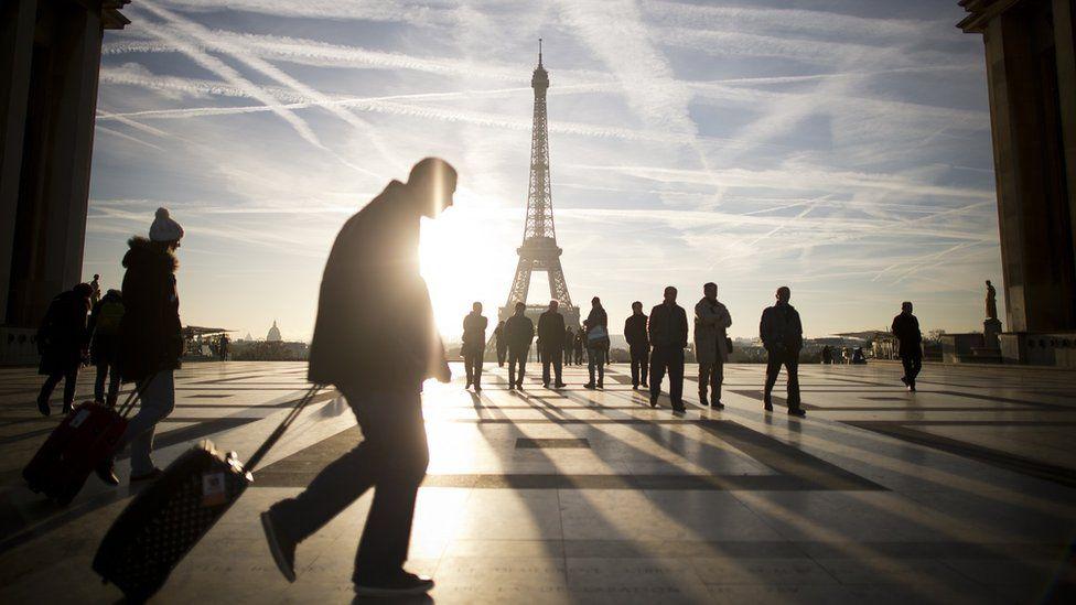 Pedestrians walking in front of Eiffel Tower