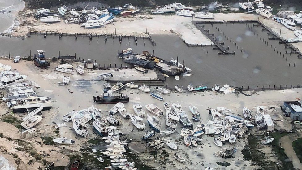 An aerial photo of a harbour with many boats pushed out of the sea and destroyed