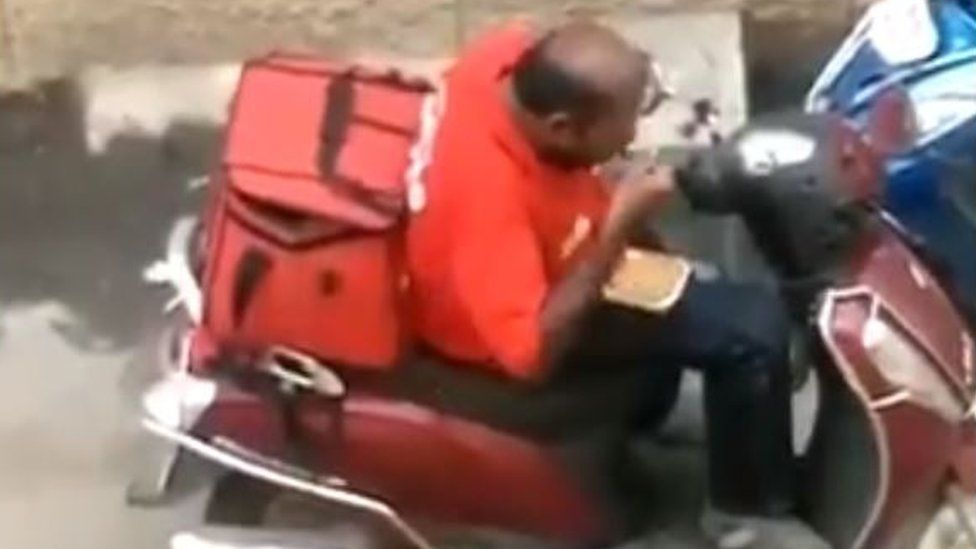 Male Zomato delivery driver eating food from a takeaway container.