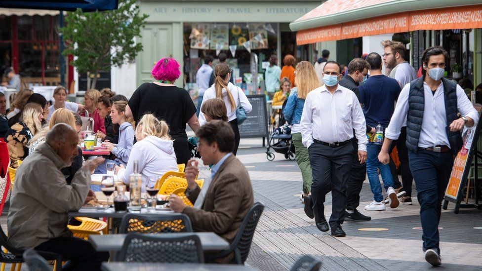 People wearing face coverings pass diners sitting at outside tables in Kensington, London