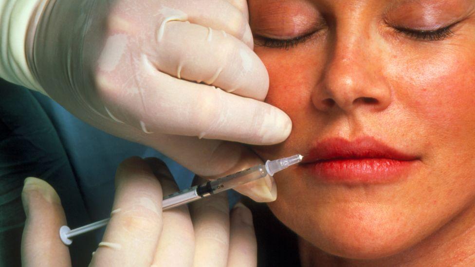 Woman having botox injection in lips