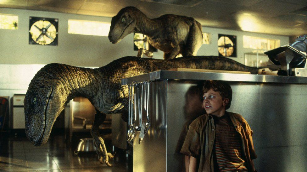 A scene from the film Jurassic Park - a young boy hides from two velociraptors in a kitchen