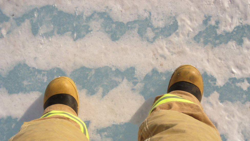 Two feet in fire-fighting gear, standing on sea ice