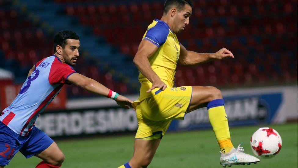 Panionios' Ehsan Hajsafi (L) vies for the ball with Tel Aviv's Eyal Golasa