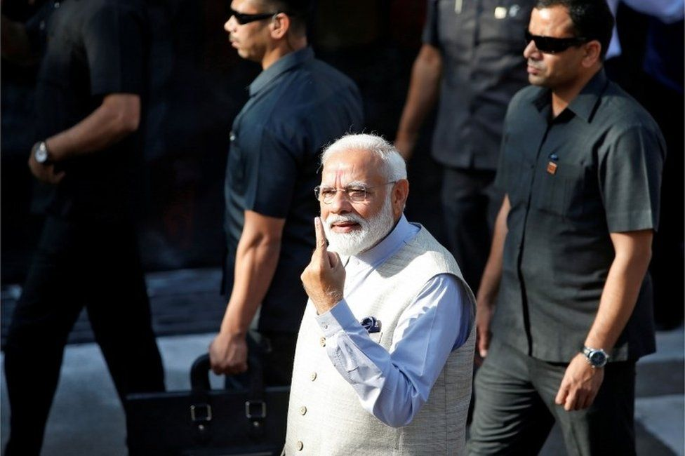 """India""""s Prime Minister Narendra Modi shows his ink-marked finger after casting his vote outside a polling station during the third phase of general election in Ahmedabad, India, April 23, 2019."""