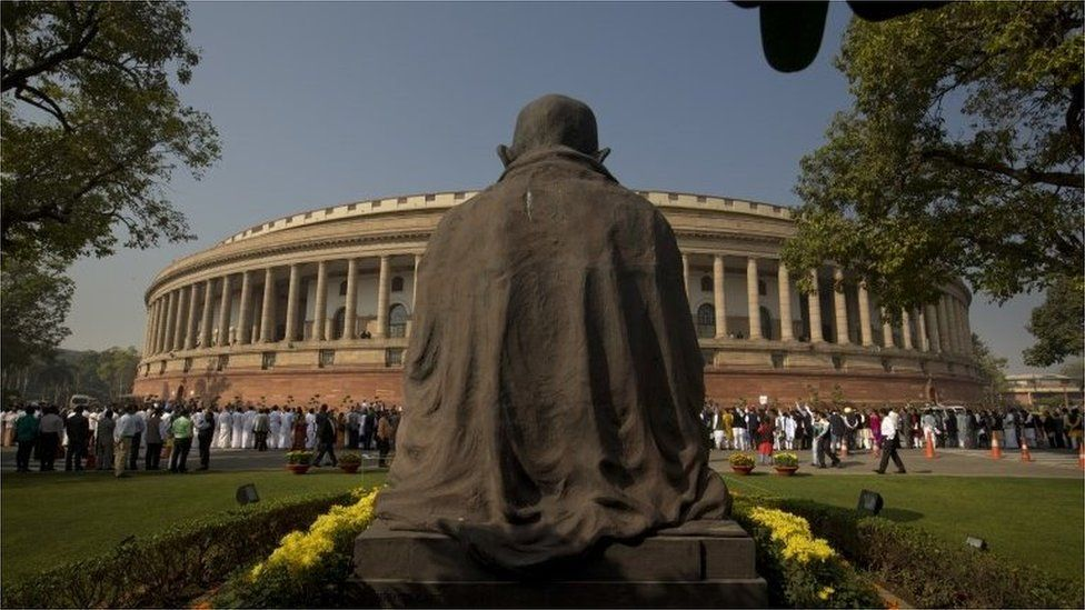 A statue of Mahatma Gandhi overlooks the Indian parliament building as lawmakers from opposition parties form a human chain to protest against the government demonetizing high-value bills in New Delhi, India, Wednesday, Nov. 23, 2016.
