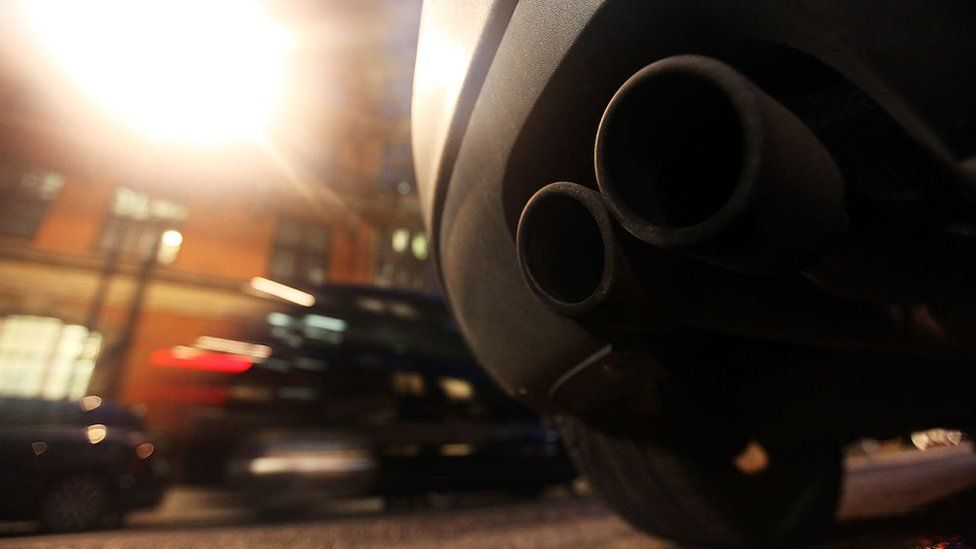 An exhaust pipe sticks out the rear of a car parked on a street