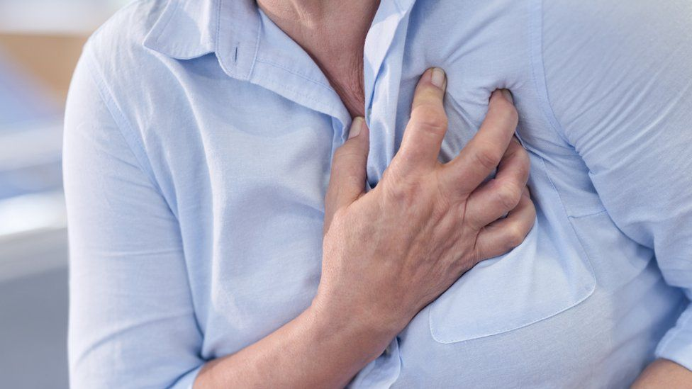 Woman clutches her chest