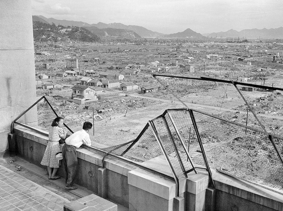 一對夫婦在被毀壞的大樓上遠眺城市廢墟。