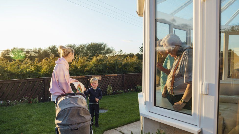 Older people wave through a conservatory to a mother with pram and a child