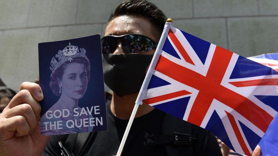 Флаг Британии фото королевы в руках протестующего