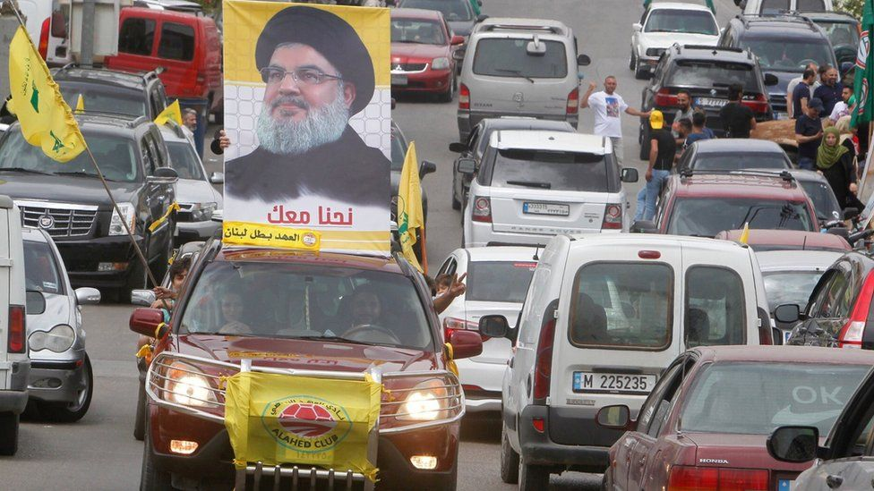 A man carries a picture of Hezbollah leader Hassan Nasrallah on election day in Bint Jbeil, in southern Lebanon, on 6 May 2018