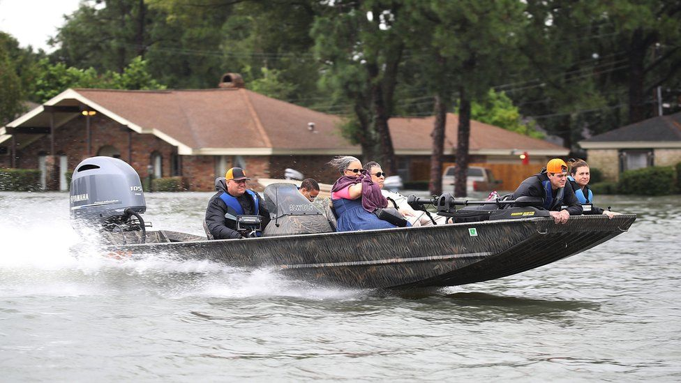 A shallow speedboat moves at high speed through a flooded street in Port Arthur, carrying evacuees