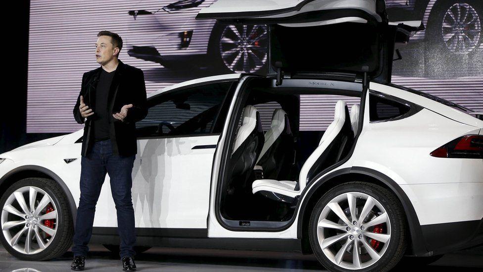 Elon Musk in front of Tesla Model X car