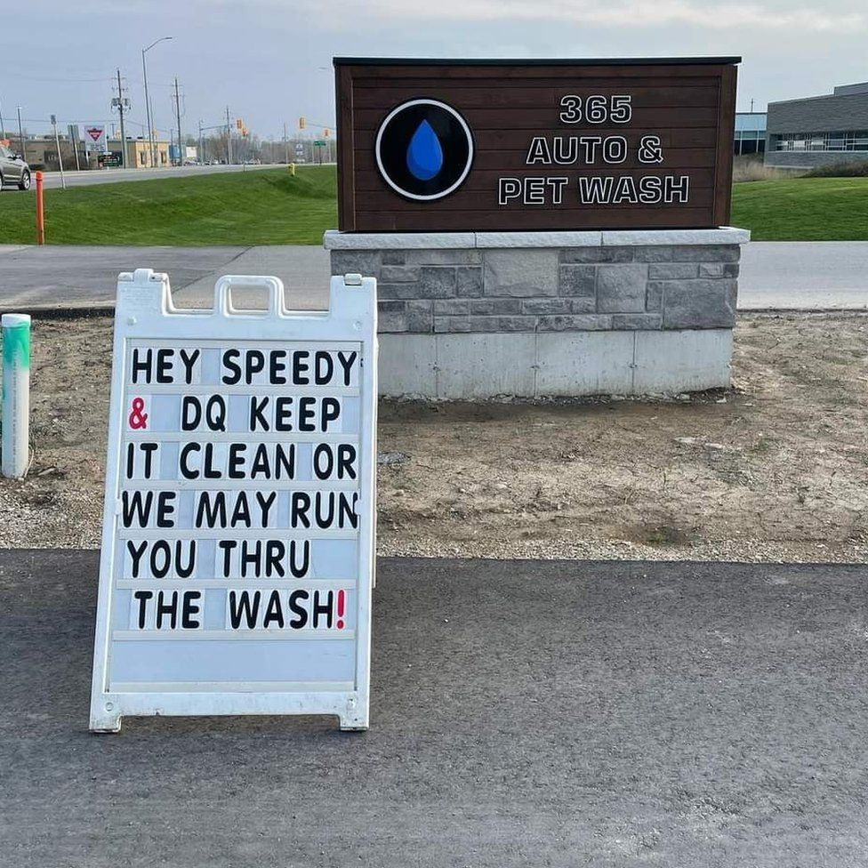 A sign at a pet wash reads 'Hey Speedy & DQ, keep it clean or we may run you through the wash'
