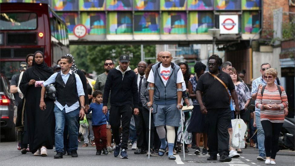 A silent march to pay respect to those killed in the Grenfell Tower disaster makes its way down Ladbroke Grove