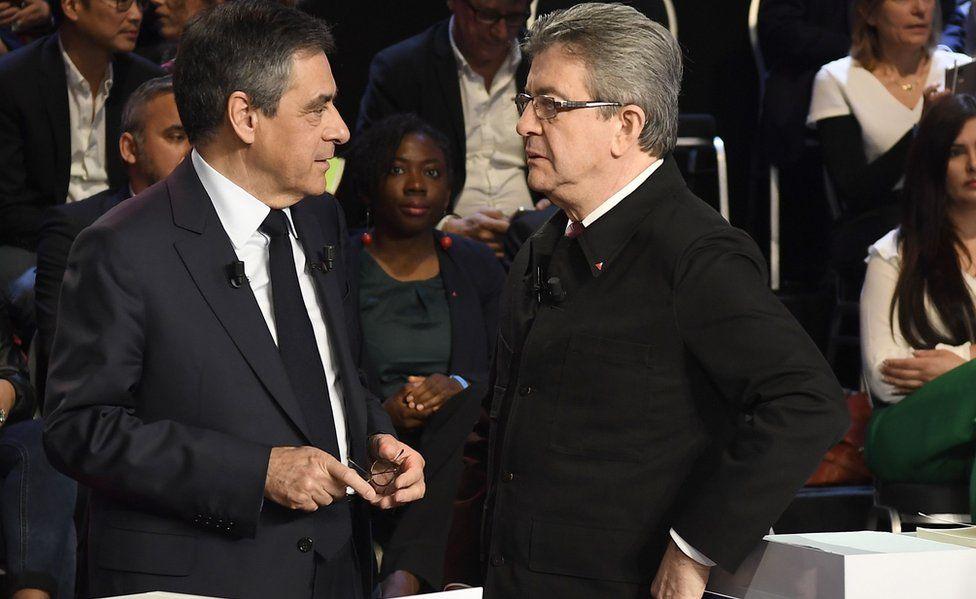 Jean-Luc Mélenchon (R) speaks with Republican candidate François Fillon