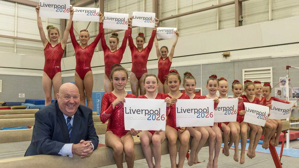 Joe Anderson with young gymnasts holding Liverpool 2026 placards
