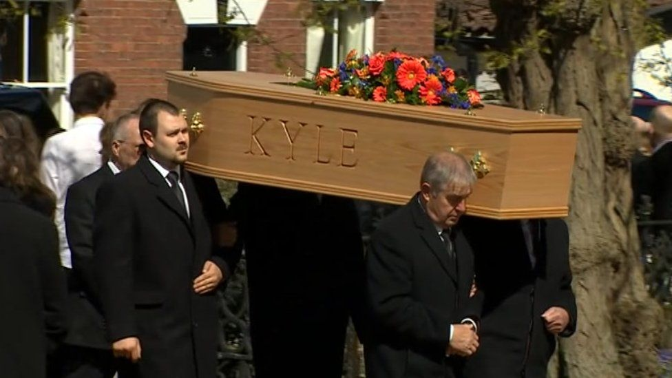 Pall bearers carry the coffin into church