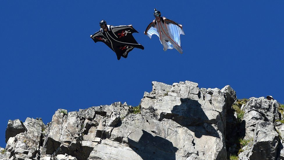Two wingsuit flyers jumping off mountain