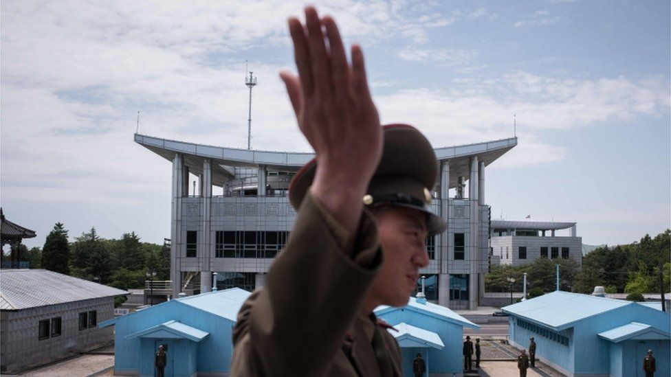 """In a photo taken on 2 June 2017 a Korean People""""s Army (KPA) soldier gestures as he stands before the military demarcation line separating North and South Korea, before South Korea""""s """"Freedom House"""" (rear C) at the Joint Security Area (JSA) near Kaesong"""