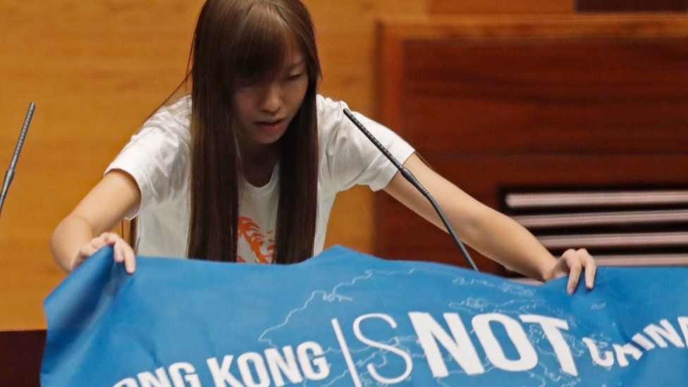 """A newly elected lawmaker, Youngspiration's Yau Wai-ching, displays a banner with words reading """"Hong Kong is not China"""" as she takes oath in the new legislature Council in Hong Kong, 12 Oct 2016"""