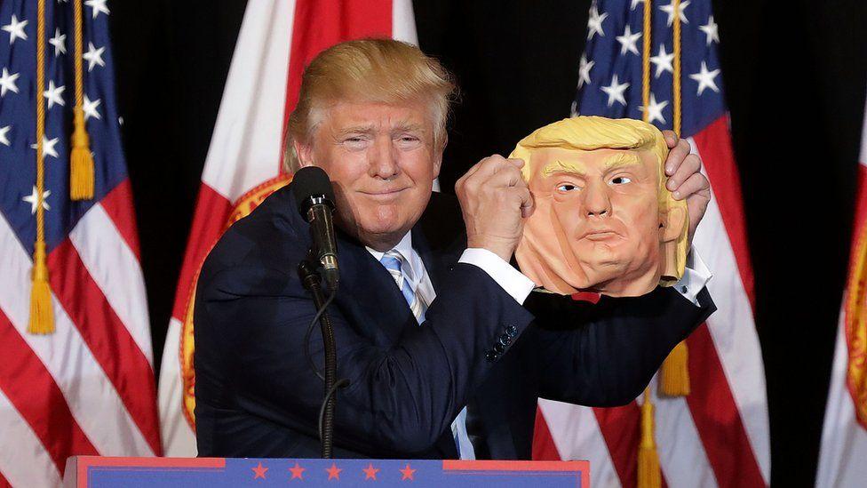 Donald Trump holds up a Donald Trump mask