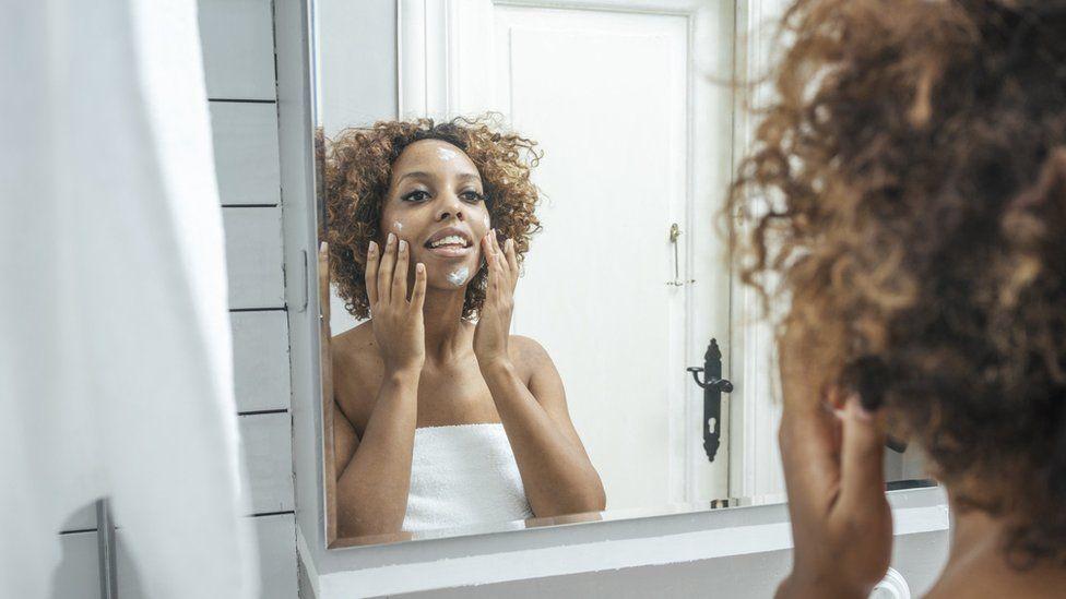 Woman using face cream.