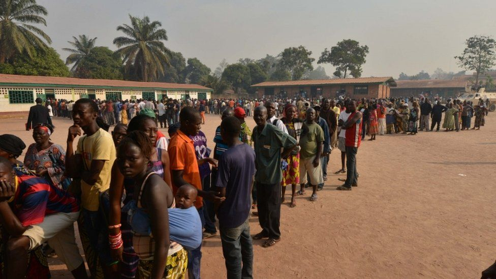 People queue outside a polling station on December 30, 2015 as they go to the polls to take part in the country's presidential and legislative in the ¨PK5 district of the capital Bangui