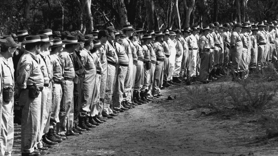 A black and white picture of dozens of police officers stood in a row ready to search a forest