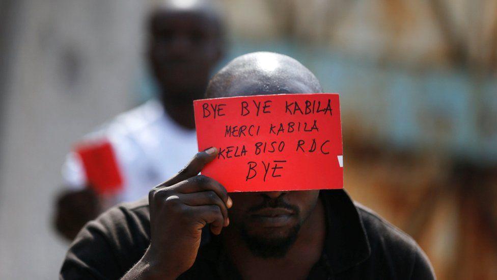 Protester holding anti-Kabila banner
