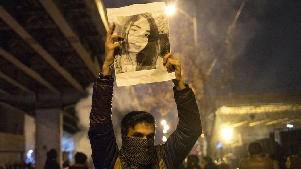 Tehran protester holding up picture