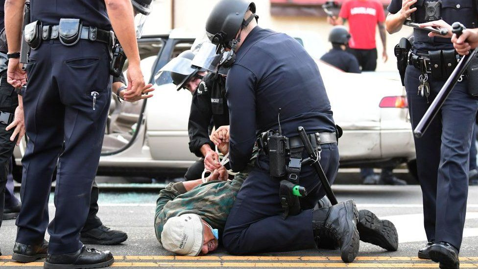A man is arrested by Los Angeles police officers for violating curfew in Hollywood