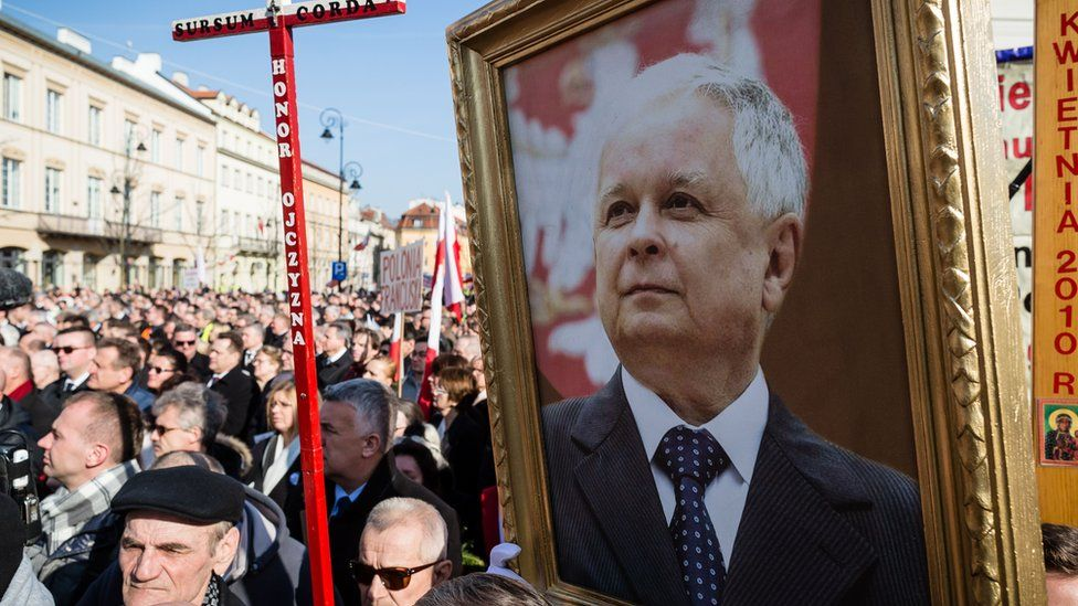 People hold a portrait of late Polish President Lech Kaczynski as they attend a ceremony marking the fifth anniversary of the presidential plane crash in Smolensk