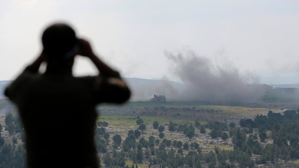 A Turkey-backed Free Syrian Army soldier watches with binoculars as smoke rises after a bomb attack during an offensive, at Der Mismis Village, southeast of Afrin, Syria.