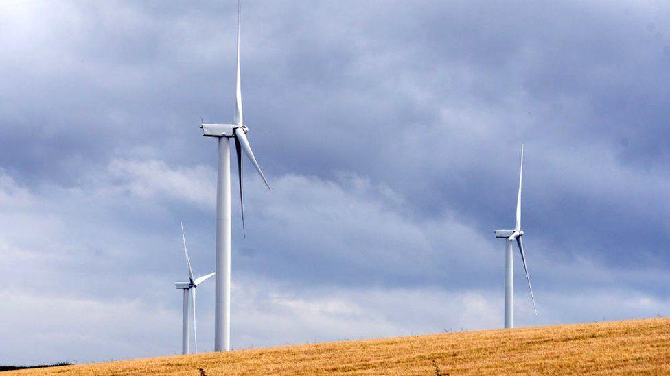 Wind turbines rise above a wheatfield in Fife