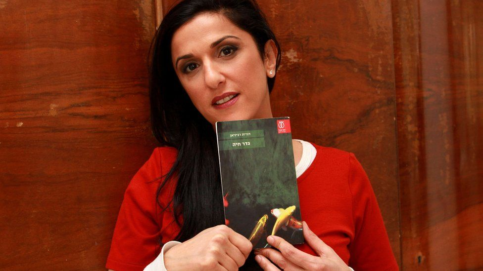 "A file picture taken on December 31, 2015, shows Israeli author Dorit Rabinyan posing with her Hebrew-language novel titled ""Gader Haya"""