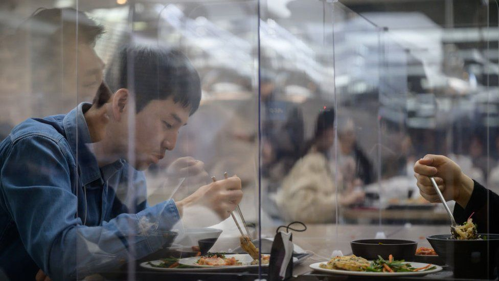Employees sit behind protective screens, as they eat in a cafeteria at the offices of Hyundai