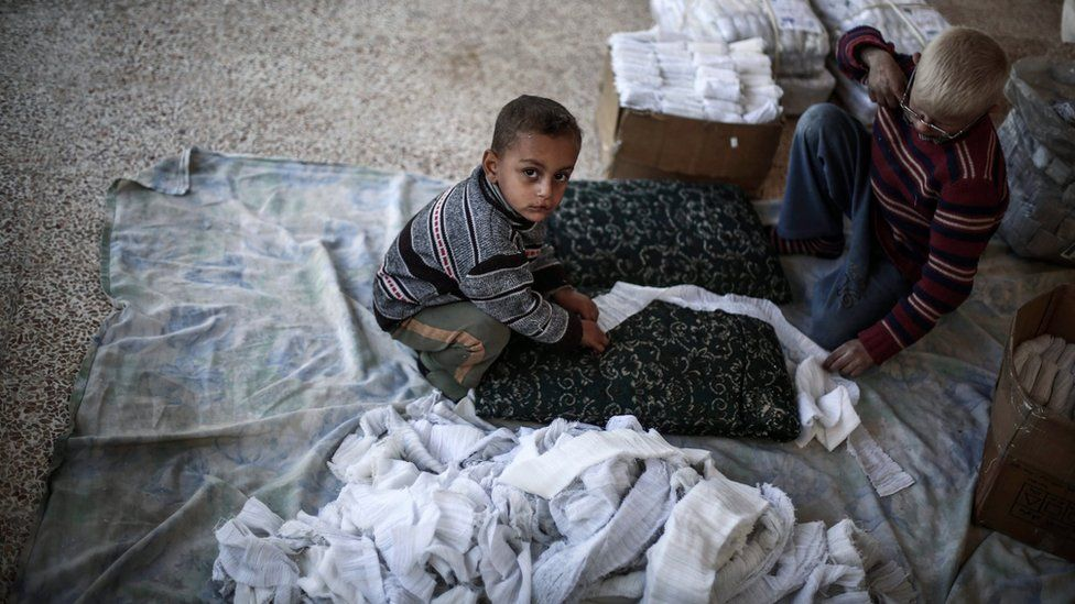 Young Syrians roll gauze for medical dressings at a small factory in rebel-held Douma, outside Damascus, Syria (6 December 2015)