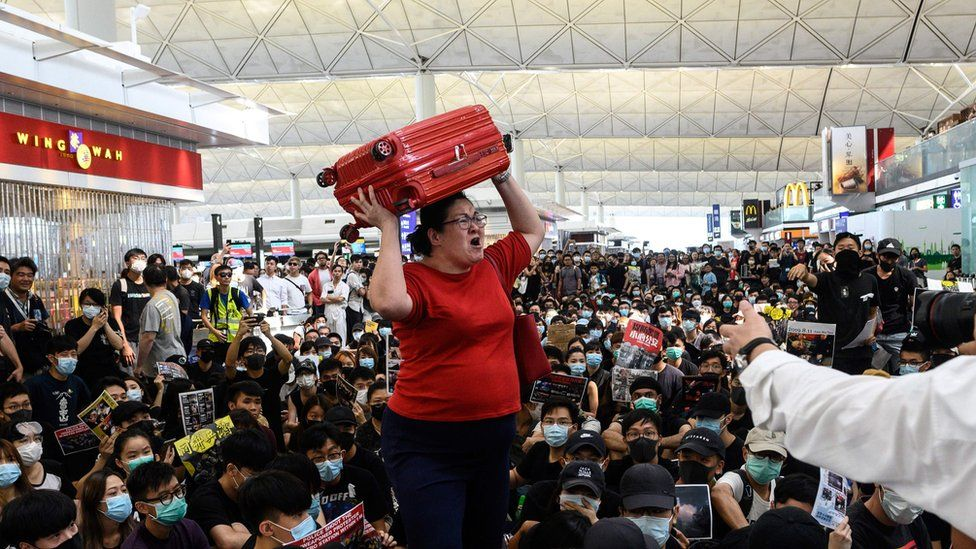 A tourist (C) gives her luggage to security guards as she tries to enter the departures gate during another demonstration by pro-democracy protesters (protestors, demonstrators) who are trying to occupy the departures hall during another demonstration at Hong Kong's international airport