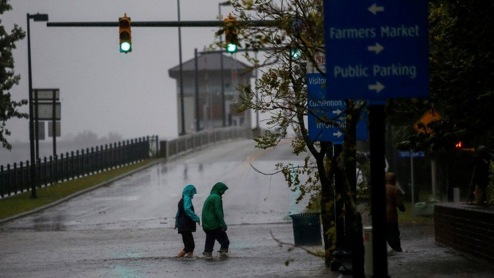 Two people walk in flooded streets in New Bern, North Carolina