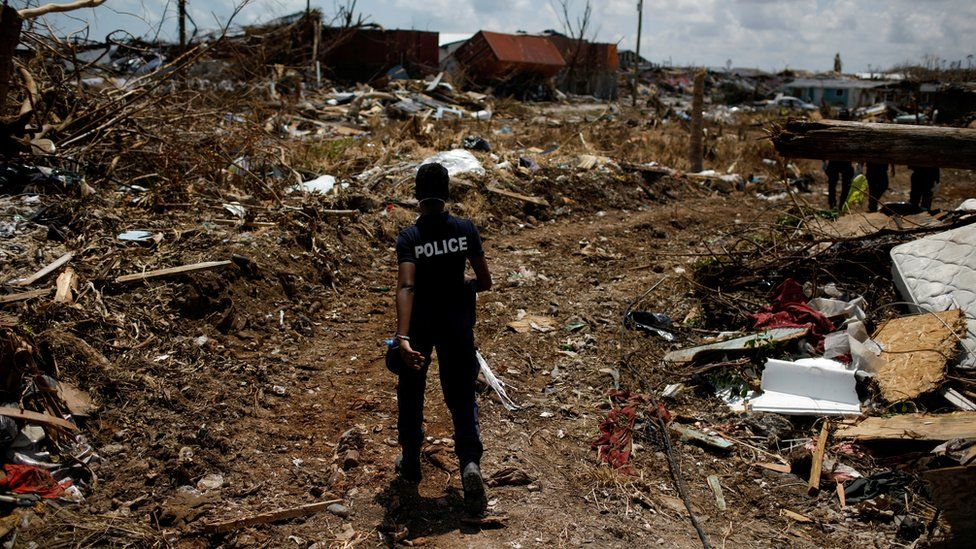 A police officer searches for the dead in the Abaco Islands