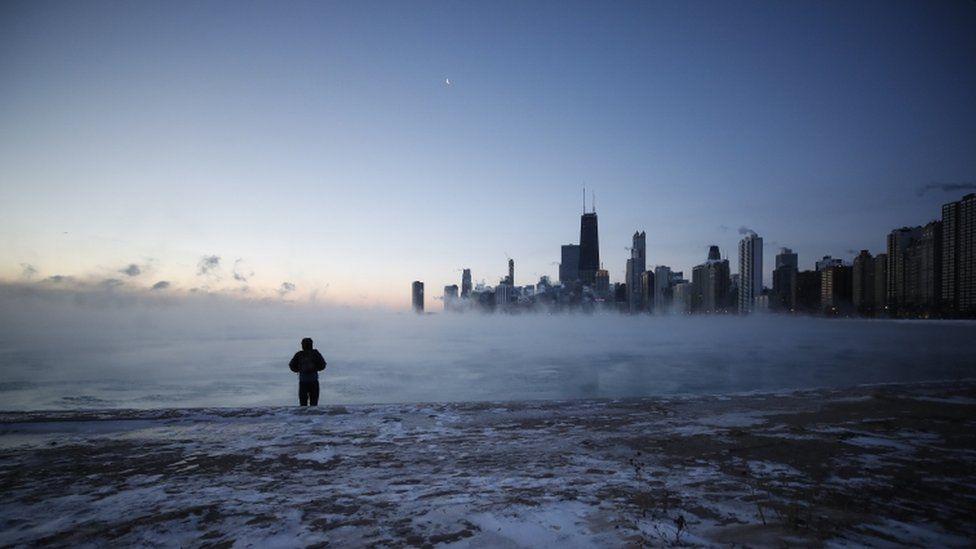A man walks on North Avenue Beach as the sun rises over Lake Michigan in Chicago, Illinois