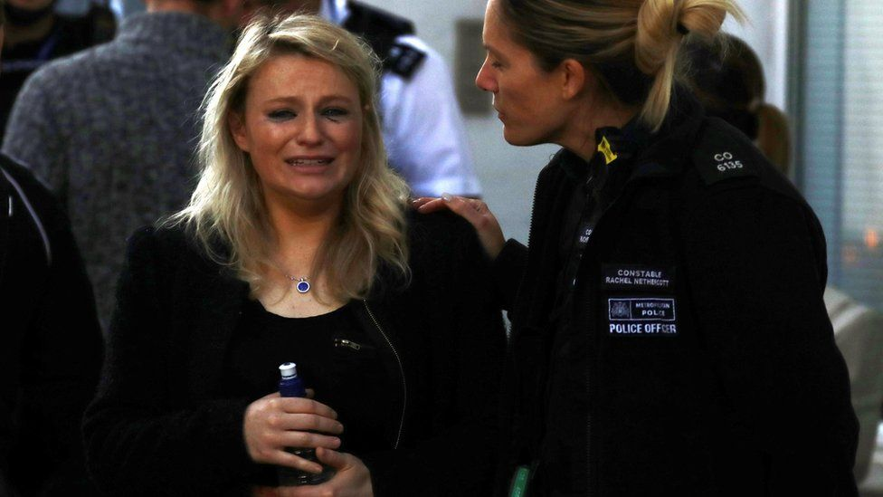 A woman was comforted by a police officer outside Parsons Green station