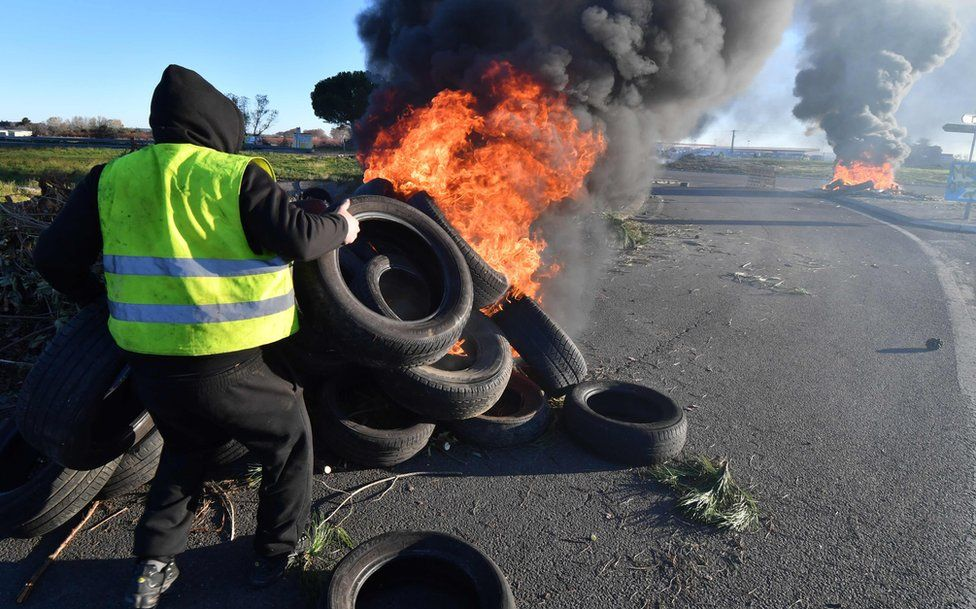 A man wearing a yellow vest burns tyres at a road blockade during a demonstration to protest against the rise in the price of oil and the cost of living, on December 11, 2018, in Aimargues, near Montpellier, southern France