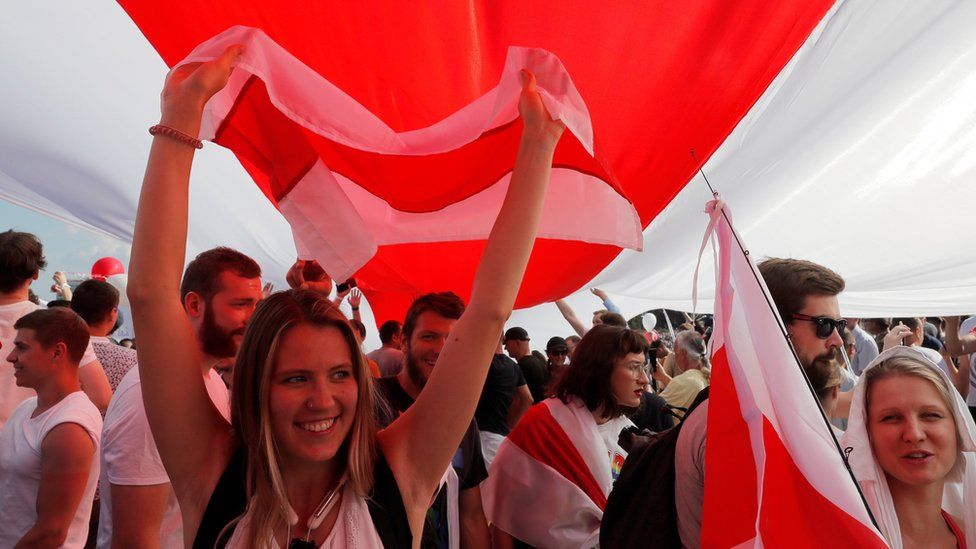 Demonstrators hold a giant historical white-red-white flag of Belarus during a protest against the presidential election results demanding the resignation of Belarusian President Alexander Lukashenko and the release of political prisoners, in Minsk, 16 August