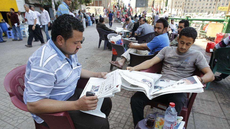 Reading papers at a Cairo cafe