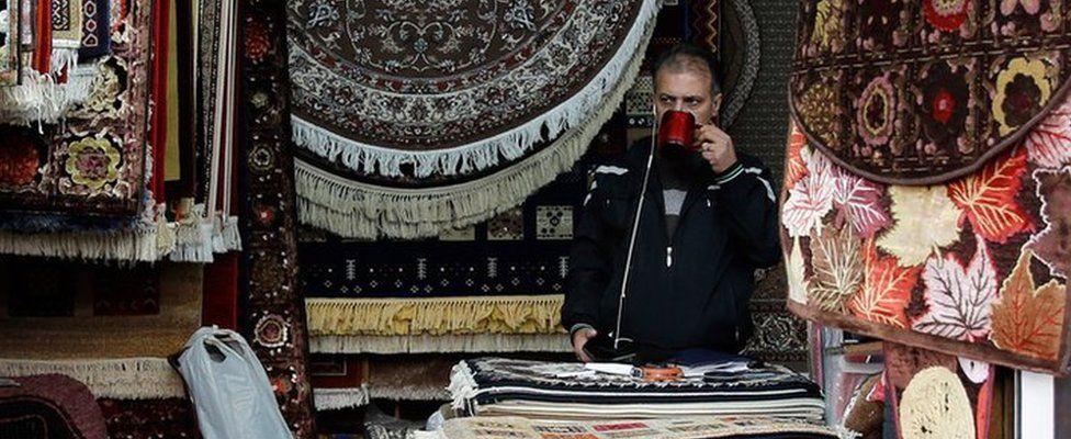 An Iranian shopkeeper at a stand in a market in Tehran, Iran, 5 November 2018
