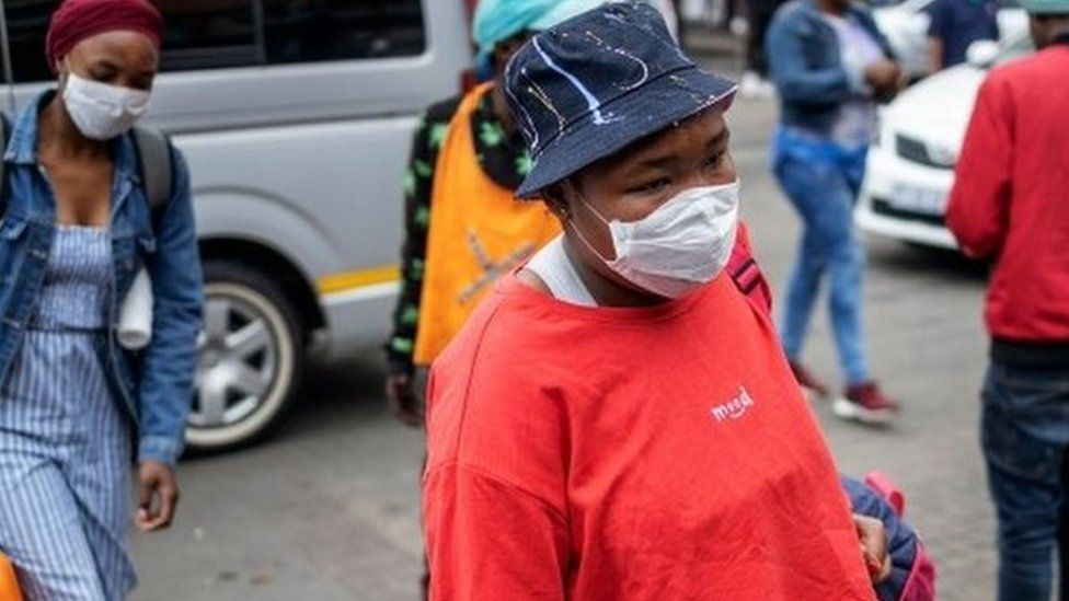 South African commuters wear masks as a preventive measure at the Wanderers taxi rank in Johannesburg CBD, on March 18, 2020.